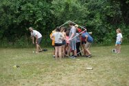 Group of campers and counselors walking through PVC pipe