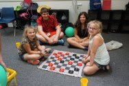 Campers and counselors playing checkers