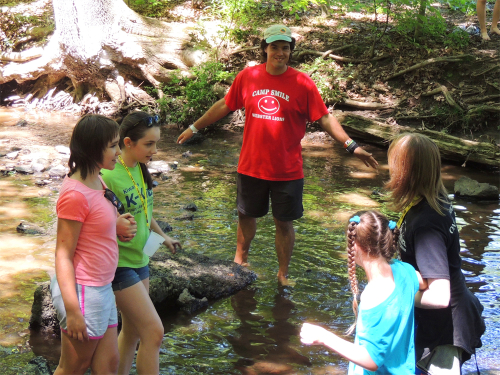 Counselors assisting campers as they walk through the water in a shallow creek