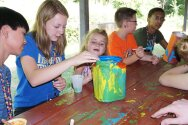 Campers and counselors painting container for totem pole craft