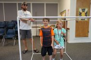 Two campers standing inside large PVC pipe cube