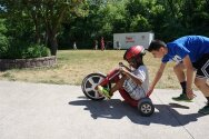 Camper trying out the tricycle with the help of his counselor