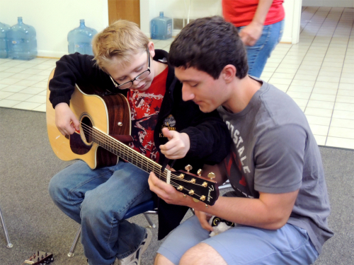 Counselor teaching a camper how to play guitar