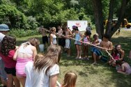 Groups holding PVC tubes together to play water relay