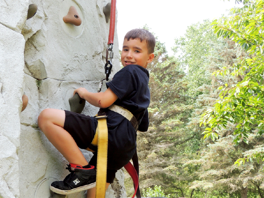 Camper climbing rock wall